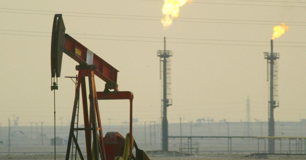 A derrick pumps in a oil field near Kuwait's border with Saudi Arabia.</p>