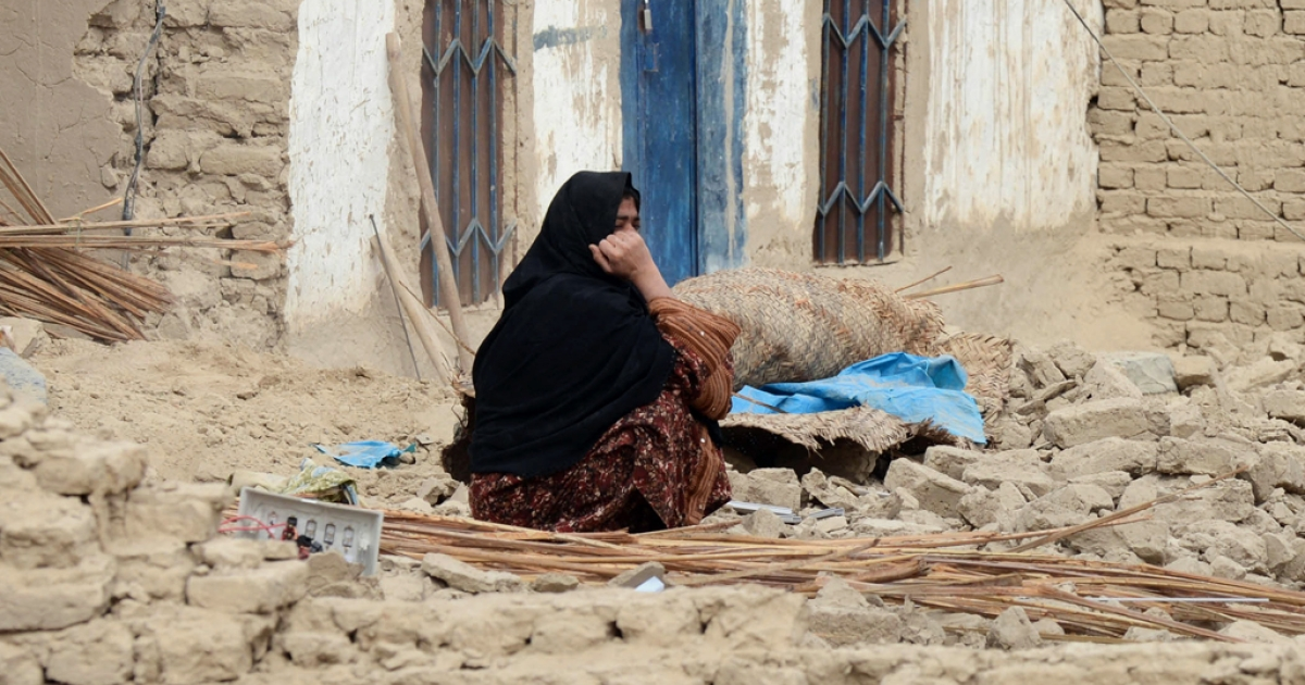 A Pakistani earthquake survivor sits near her collapsed mud house in the southwestern Baluchistan province on April 17, 2013. Another earthquake struck the same region on September 24, 2013.</p>