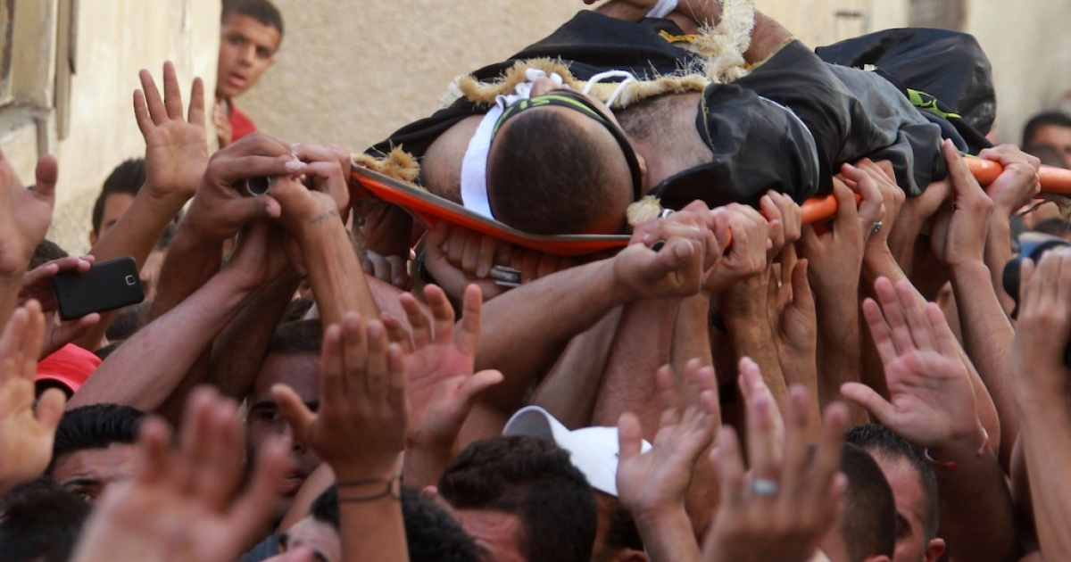 Palestinians mourners carry the body Islam Tubasi during his funeral in the West Bank refugee camp of Jenin on September 17, 2013. Israeli troops shot and fatally wounded a suspected Palestinian militant during a raid on his home in a West Bank refugee camp, the army and Palestinian security officials said.</p>