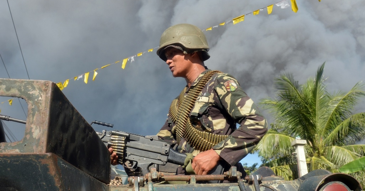 A Philippine soldier standing in an armoured personnel carrier adjusts his machine gun prior to an assault on Muslim rebel positions as the stand-off in the southern city of Zamboanga enters its fifth day on Sept. 13, 2013.</p>