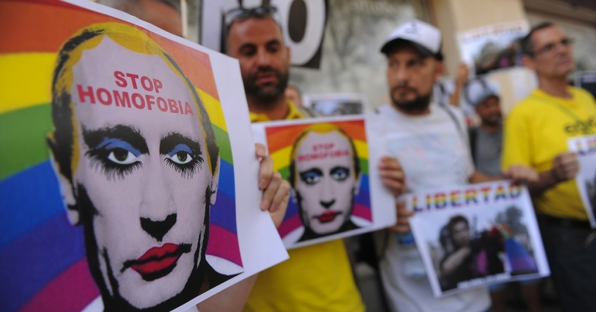 Protestors hold images of Russian President Vladimir Putin wearing lipstick during a protest against Russian anti-gay laws opposite the Russian embassy on Aug. 23, 2013 in Madrid, Spain.</p>