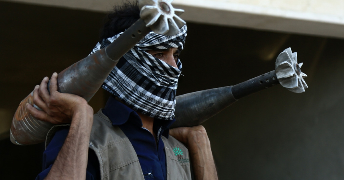 A rebel fighter carries homemade mortar rounds on Sept. 3, 2013 in the northern Syrian city of Raqqa.</p>