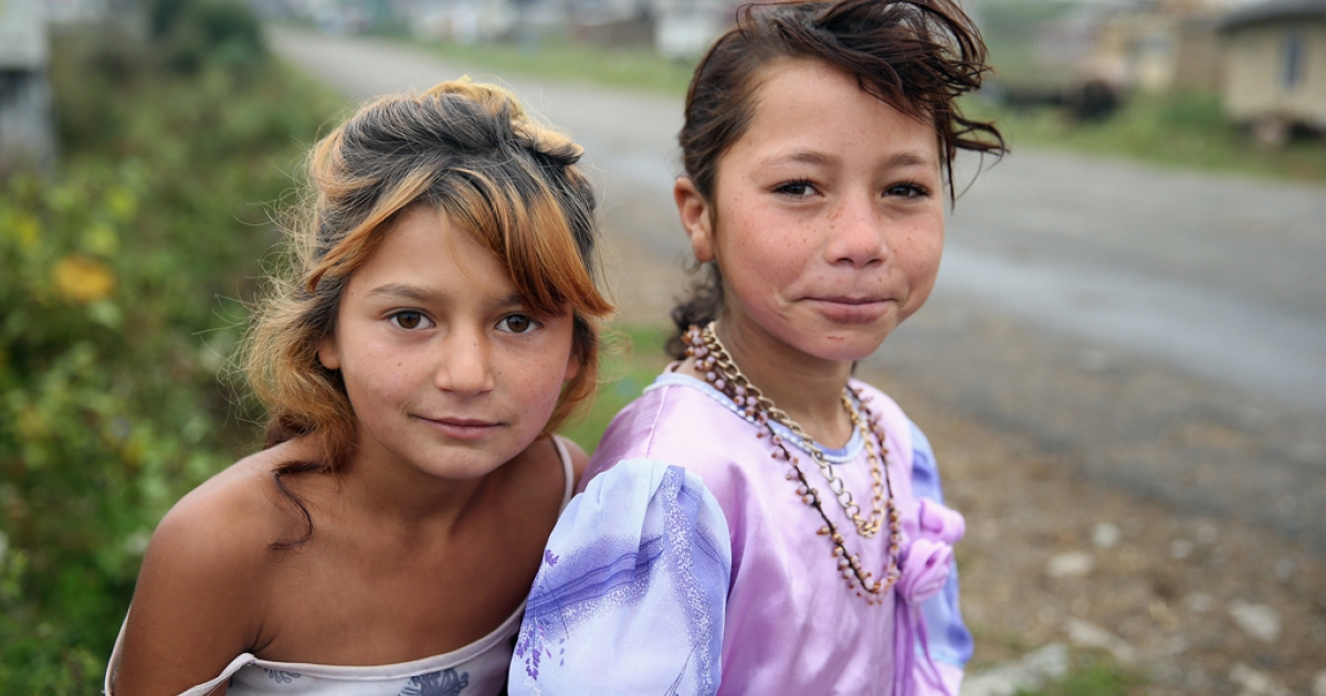 Roma children Andrea-Maria (L) and Valeria sit next to the only street that goes by the abjectly poor Roma settlement of Ponorata on September 10, 2013 in Ponorata, Romania.</p>