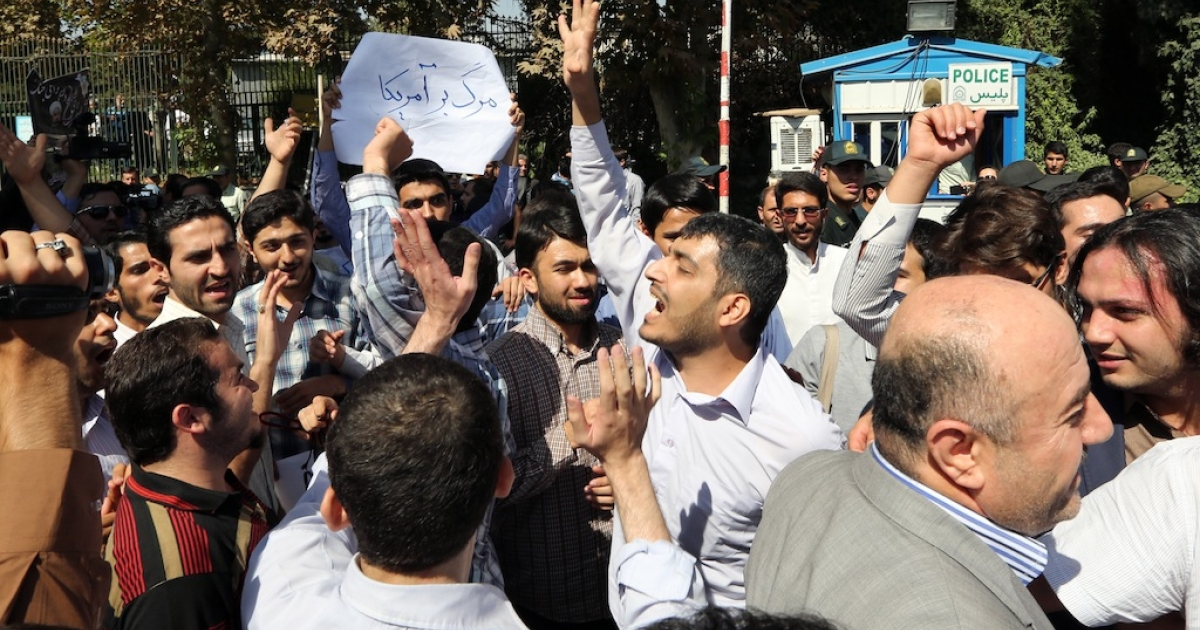 Iranian supporters of the Basiji militia shout anti US slogans as Iranian president Hassan Rouhani arrived from New York, on September 28, 2013 in Tehran. Some 60 hardline Islamists chanted 'Death to America' and 'Death to Israel' but they were outnumbered by 200 to 300 supporters of the president who shouted: 'Thank you Rouhani.'</p>