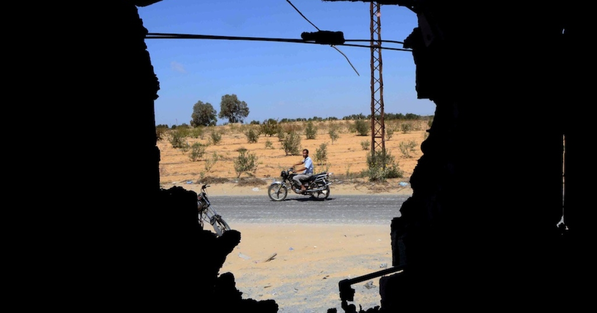 A man is seen riding a motorbike through a wall that was destroyed by the Egyptian Army the day before in a village on the outskirt of the Northern Sinai town of Sheik Zuweid on Sept. 10, 2013.</p>