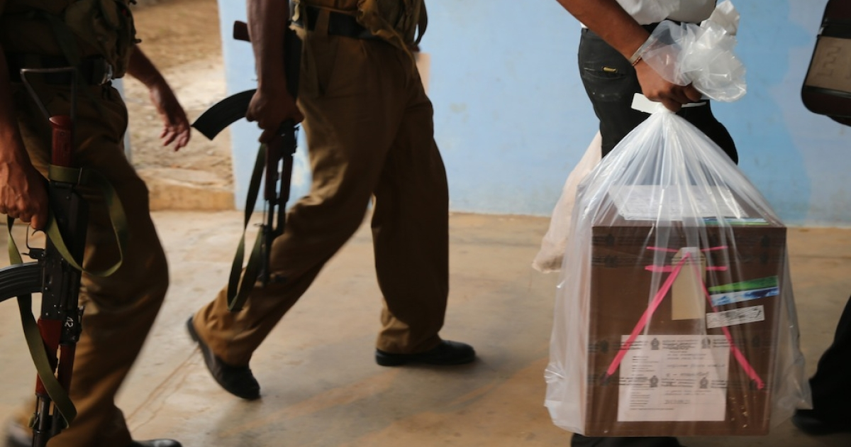 A Sri Lankan poll officer carries a sealed ballot box while escorted by police at counting center on September 21, 2013 in Jaffna, Sri Lanka. Ethnic Tamil voters in Sri Lanka's war-ravaged north went to the polls on September 21, to form their first functioning provincial government since 1988, following 26-year long civil war that ended in 2009.</p>