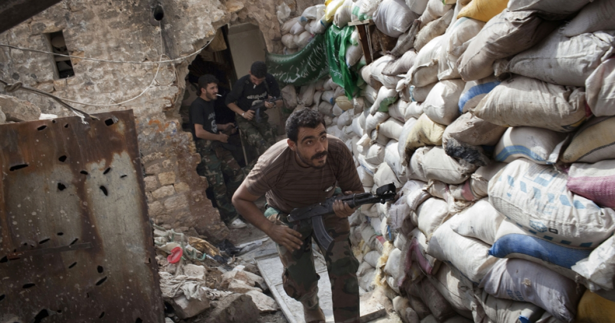 Rebel fighters duck as they run behind a barricade to avoid being fired at by Syrian regime forces in the Old City's front line in Aleppo on September 18, 2013.</p>
