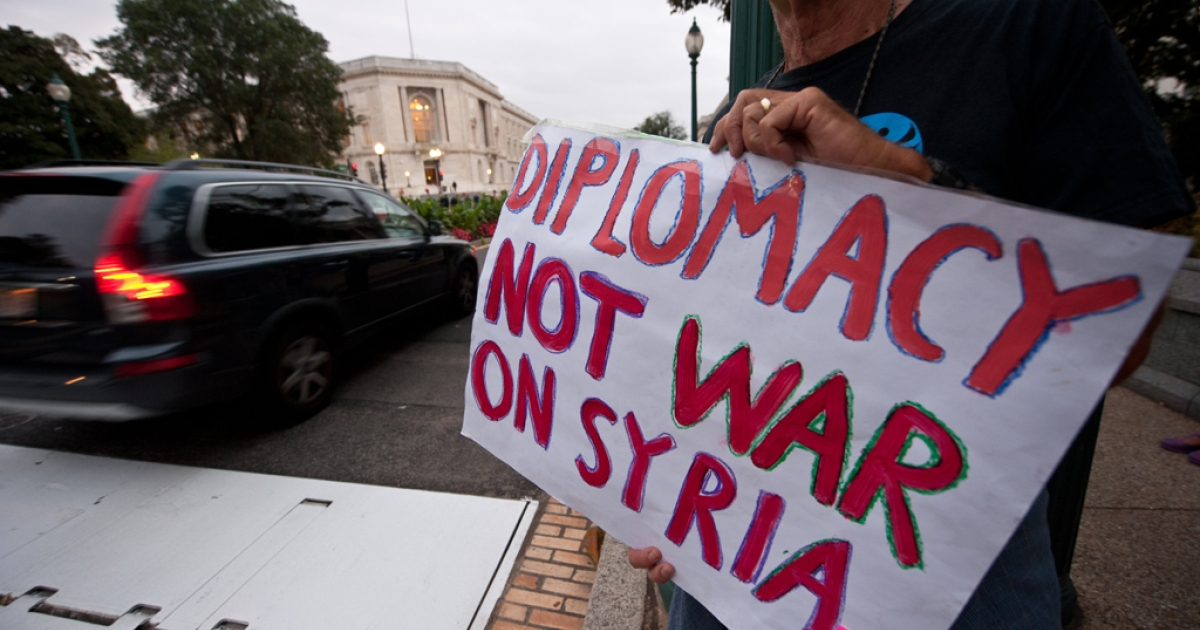 People protest against a US military intervention in Syria in front of the Cannon House Office Building near the US Capitol as mebers of the US Congress leave an administration briefing on Syria to lawmakers in Washington on September 9, 2013.</p>