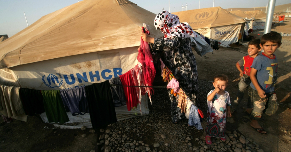 A Syrian-Kurdish refugee woman hamgs out her laundry on a clothesline outside a tent provided by the UNHCR at the Quru Gusik refugee camp in the Kurdish region of northern Iraq.</p>