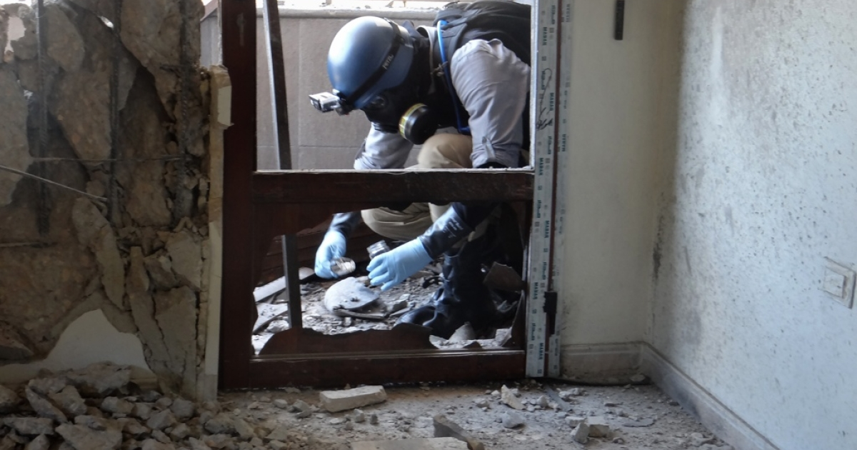A UN arms expert collects samples in a Damascus suburb Aug. 29 during an investigation into chemical weapons attacks.</p>