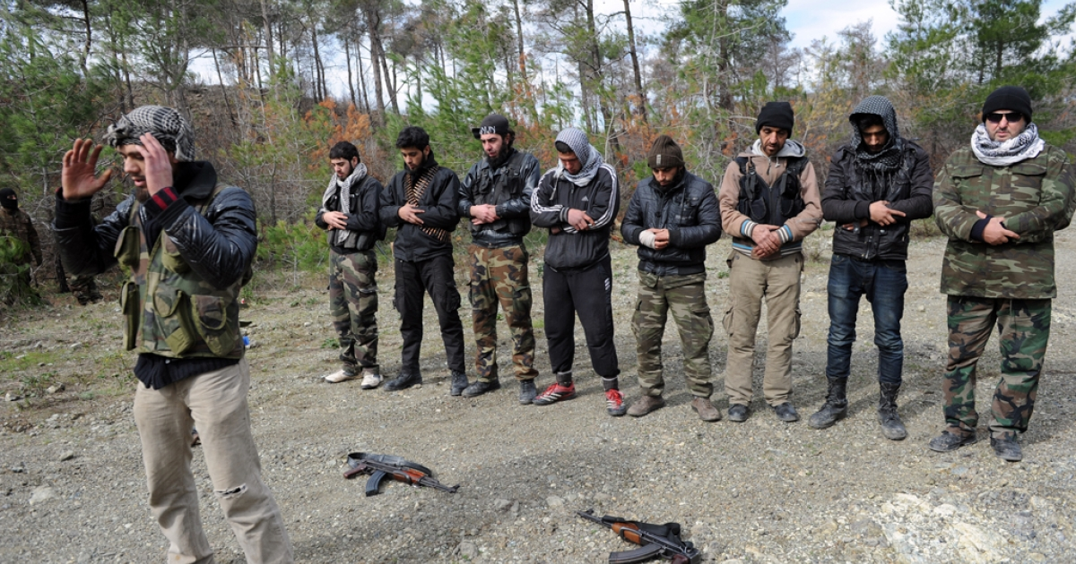 Rebel fighters pray close to their position as they prepare to fight against pro-Syrian regime forces on the Jabal al-Turkman mountains in Syria's northern Latakia province, on February 5, 2013.</p>