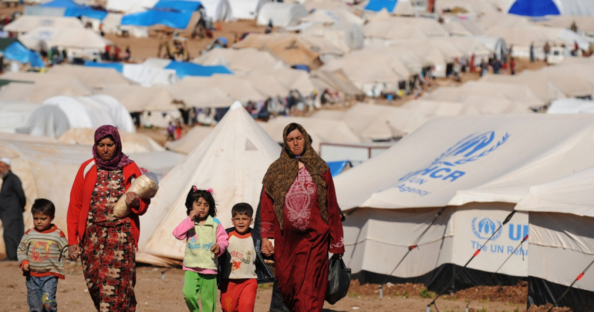 Syrian internally displaced people walk in the Atme camp, along the Turkish border in the northwestern Syrian province of Idlib.</p>