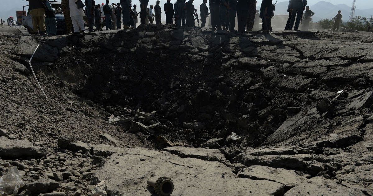 Afghan policemen and villagers look on near a crater at the scene of suicide attack in Maidan Shar, the capital city of Wardak province south of Kabul, on Sept. 8, 2013. At least four Afghan intelligence agents were killed and dozens of civilians were wounded when a group of Taliban militants attacked an intel office there.</p>