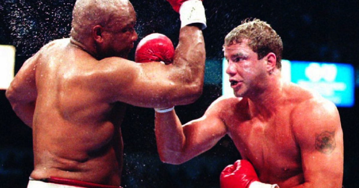 LAS VEGAS, NV - JUNE 8: Sweat flies from the head of boxer George Foreman of the U.S. (L) as Tommy Morrison of the U.S. lands a punch during their 12-round match 07 June 1993.</p>