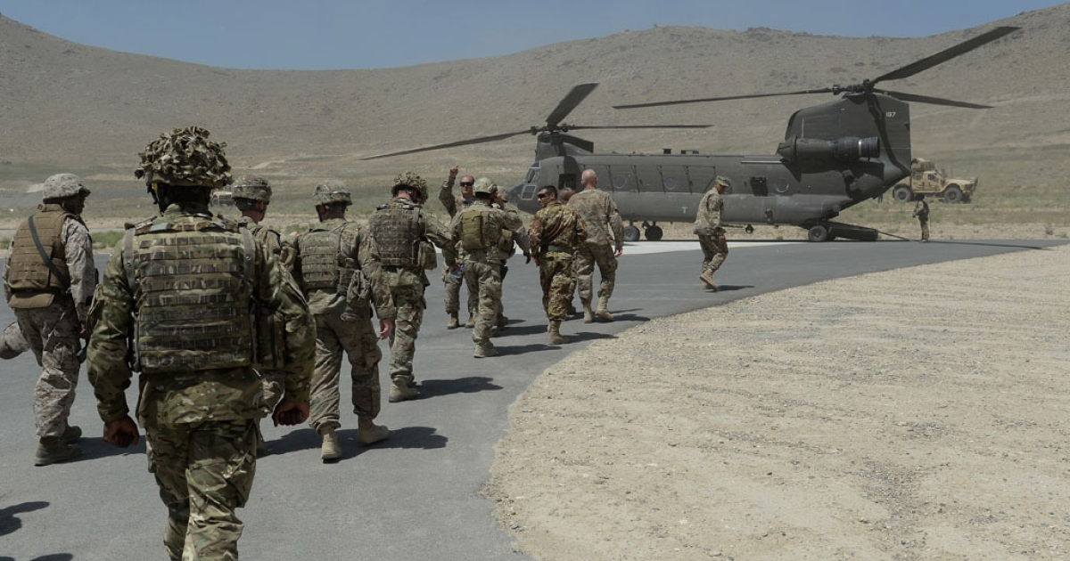 NATO soldiers board a Chinook helicopter after a security handover ceremony at a military academy outside Kabul in 2013.</p>