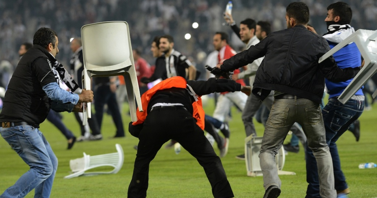Besiktas football team supporters fight with anti riot police officers during the Turkish super league football match Besiktas vs Galatasaray on Sept. 22, 2013, at the Ataturk stadium in Istanbul.</p>