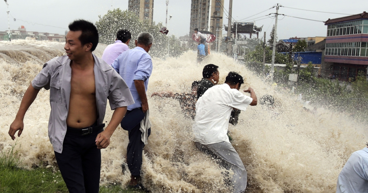 This picture taken on August 22, 2013 shows onlookers being washed away from huge waves from the