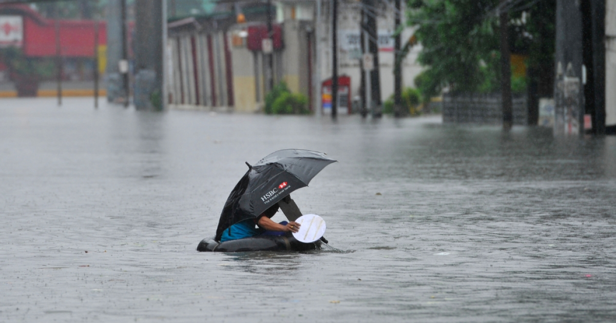 A resident using a innertube as a makeshift raft paddles through chest-deep floodwaters along a street in Manila on September 23, 2013, after torrential rains pounded Luzon island worsened by Typhoon Usagi. Monsoon rains worsened by Typhoon Usagi pounded the Philippines for the third day on September 23, causing floods and landslides that left six people dead and others stranded on rooftops, officials said.</p>