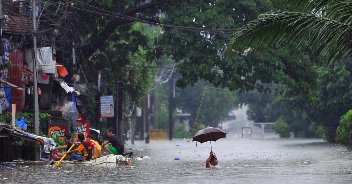 A man wades through chest-deep floodwaters along a street while his neighbors (L) paddle an improvised life raft in Manila on Sept. 23, 2013, after torrential rains worsened by Typhoon Usagi pounded Luzon island.</p>
