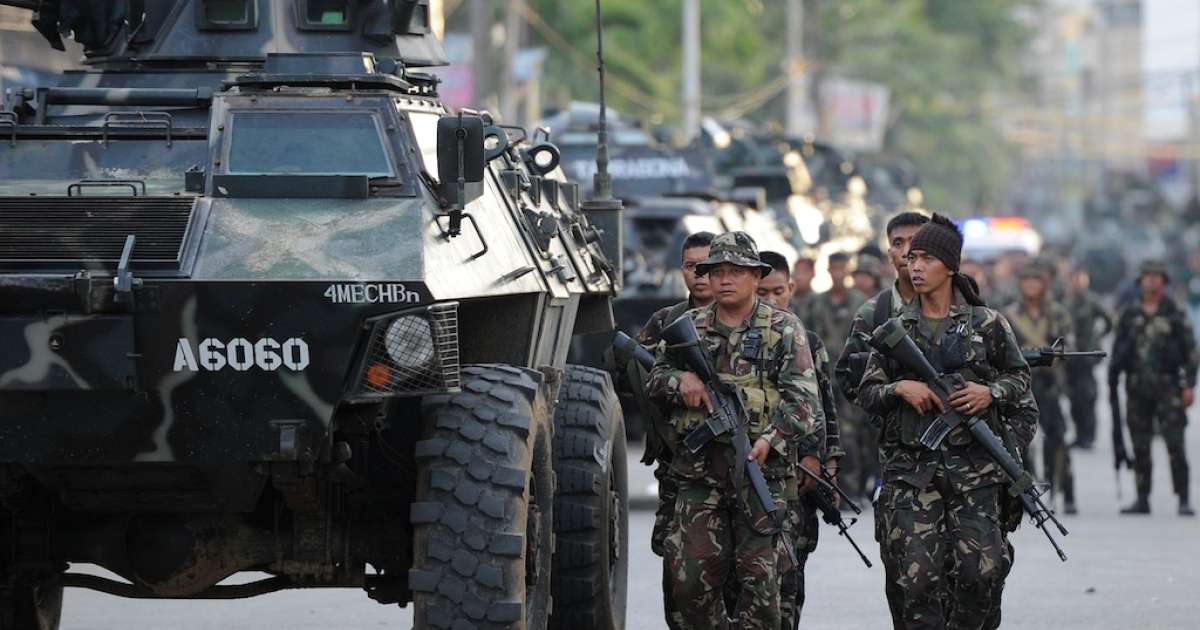 Philippine army troops walk with an armored personnel carrier as they take positions during a standoff with Muslim gunmen in Zamboanga City, on Sept. 10, 2013.</p>