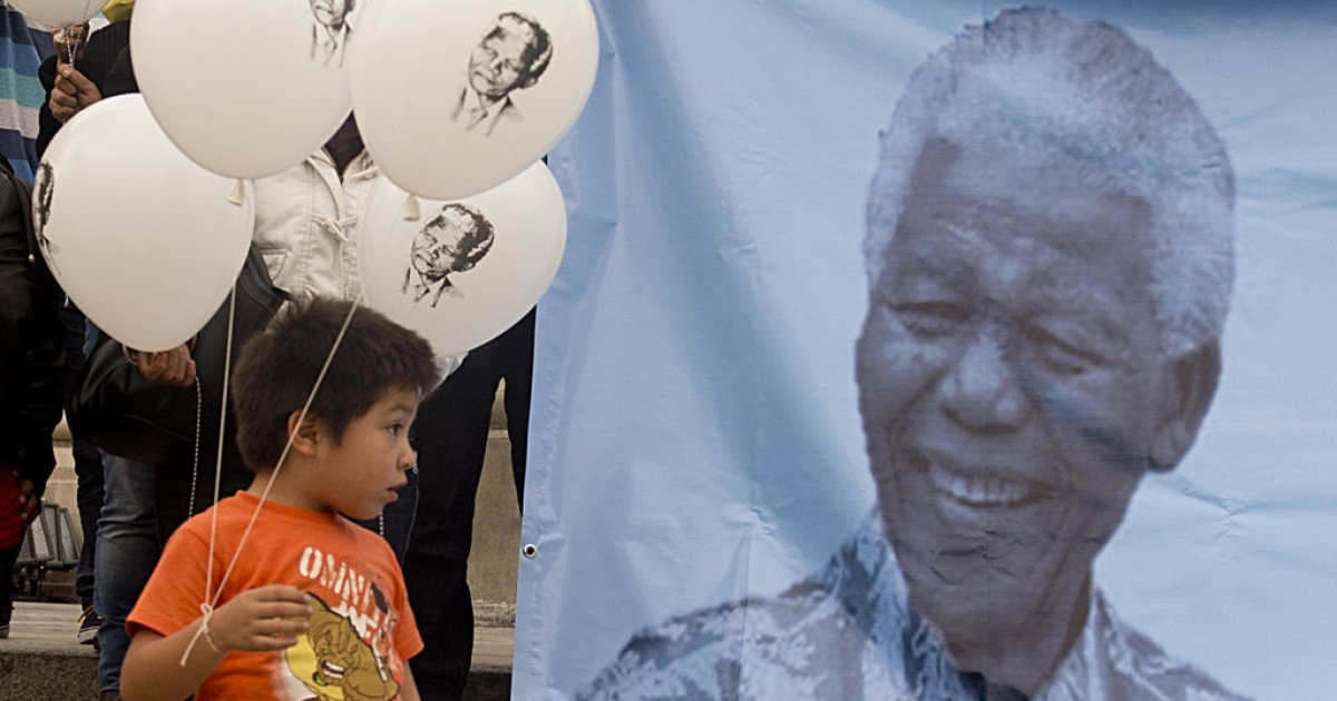 A boy accompanying his mother, member of the Conscience and Dignity Foundation, holds balloons with an image of former South African President Nelson Mandela during an event to mark Nelson Mandela International Day at Independence Angel square in Mexico City on July 18, 2013.</p>