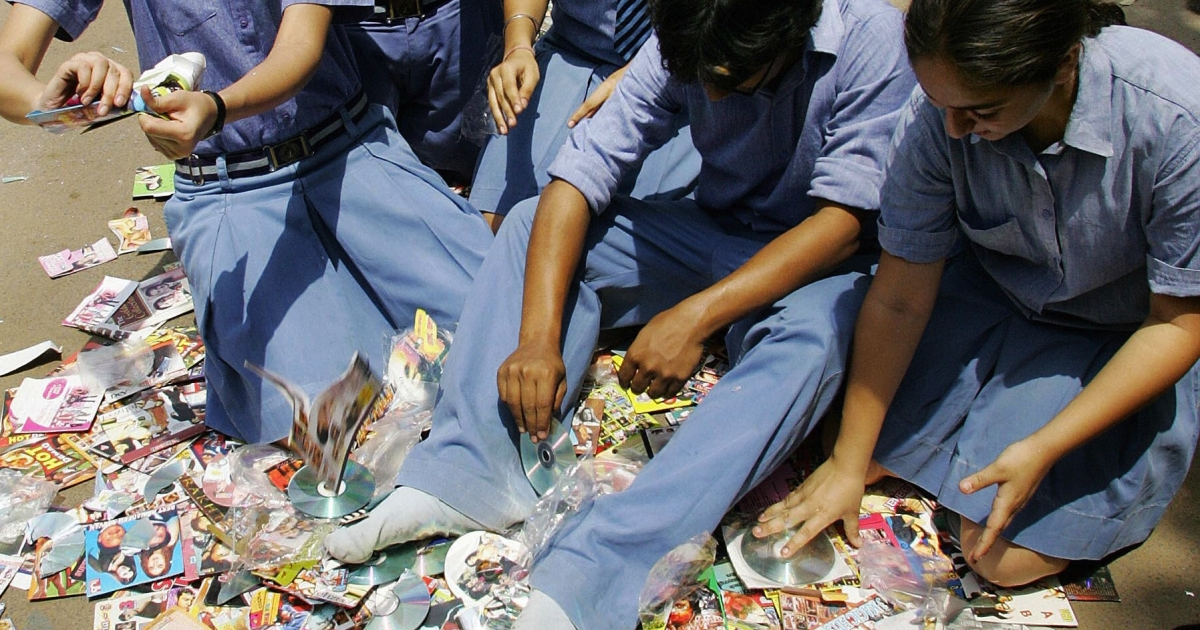 Students destroy pirated films and software during an anti-piracy protest in New Delhi on April 29, 2006</p>