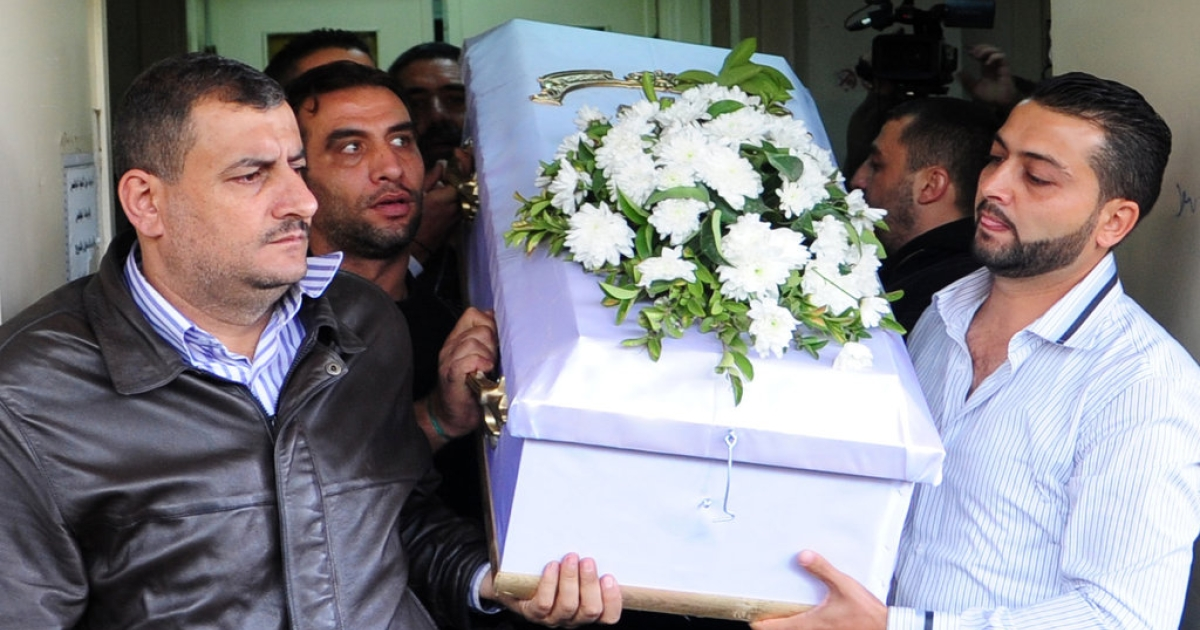 Mourners carry the coffin of one of the children killed the day before when mortar rounds hit a school bus on November 12, 2013 outside al-Moujtahed Hospital in the Syrian capital Damascus. Four students were killed when a mortar hit the vehicle they were riding in.</p>