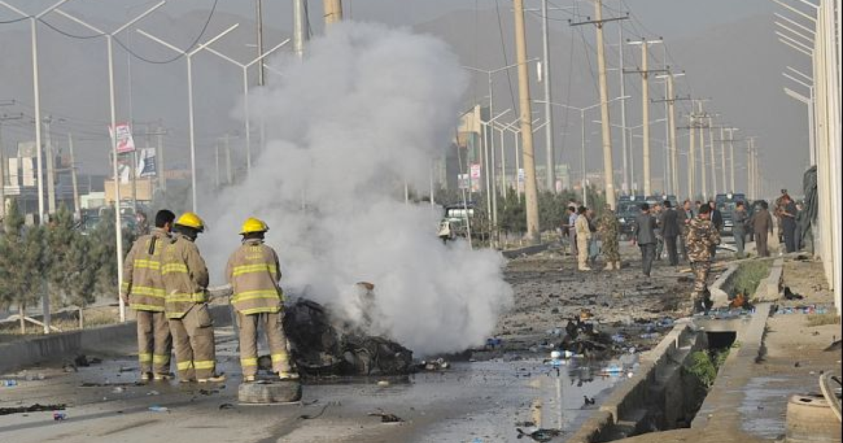 Afghanistan firefighters pour water on the remains of a vehicle that carried suicide attackers at the site of a bombing in Kabul on Sept. 18, 2012.</p>