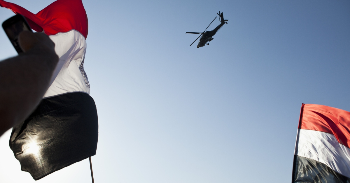 An Egyptian Army Apache helicopter flies over a crowd of pro-military demonstrators at Tahrir Square.</p>