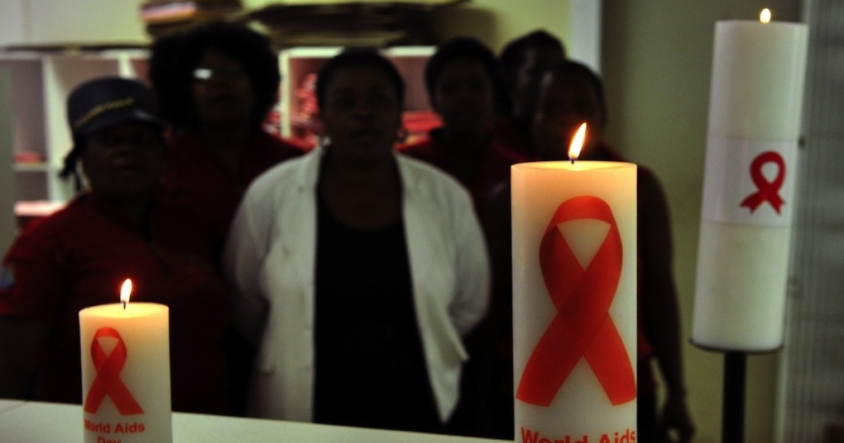 Photo taken on November 28, 2013 shows staff members of the Themba Lethu Clinic in Johannesburg, the largest antiretroviral treatment site in the country, posing behind candles commemorating World Aids Day (December 1). South Africa has been hailed as a model for HIV treatment, but some now fear its very success may be breeding complacency and making people less careful about infection.</p>