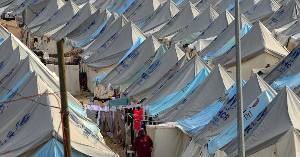A Syrian refugee woman walks among tents at Karkamis' refugee camp on January 16, 2014 near the town of Gaziantep, south of Turkey.</p>