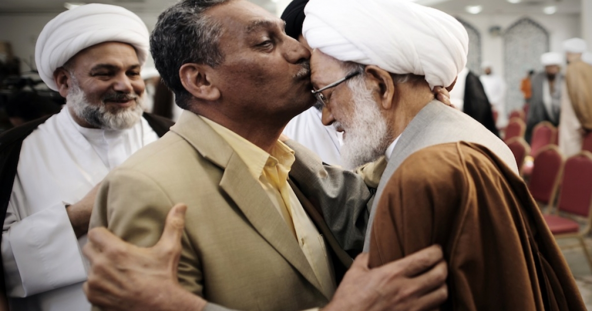A Bahraini man kisses the forehead of Sheikh Isa Qassim (R), top senior Shiite cleric, during a protest against the closing down of a Shiite Muslim clerics' council earlier this week, at a mosque in the capital Manama, on February 2, 2014. A Bahraini court ordered the closure of the Olamaa Islamic Council and the liquidation of its assets following a lawsuit by the ministry of justice, Islamic affairs and endowments, a judicial source said.</p>