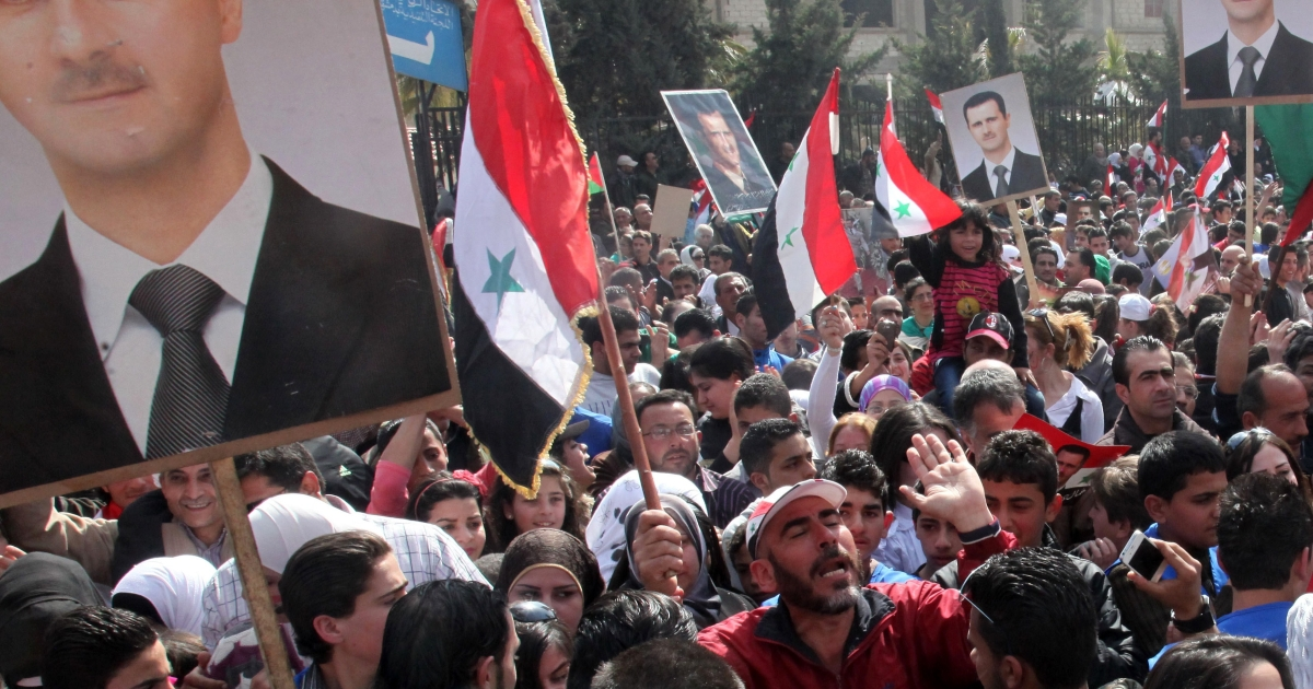 Syrians holding portraits of President Bashar al-Assad and waving national flags take part in a rally to show their support to the government on February 22 in Damascus.</p>