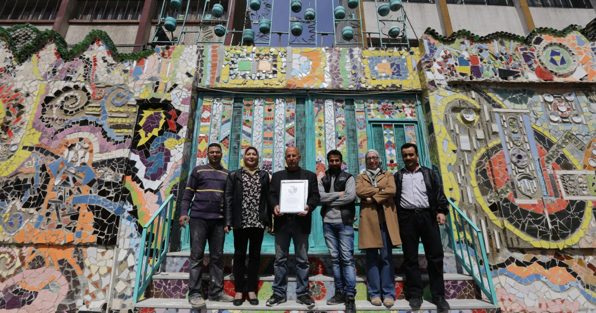 Syrian Moaffak Makhoul and a team of six artists pose with their Guinness World Records award for the largest mural made from recycled material, on March 31, 2014 in Damascus's al-Mazzeh neighborhood.</p>