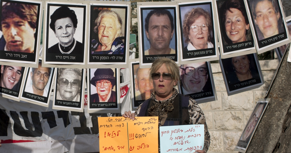 An Israeli woman holds signs in front of pictures of Israelis who were killed by Palestinians militants during a Jerusalem protest against the release of Palestinian prisoners.</p>