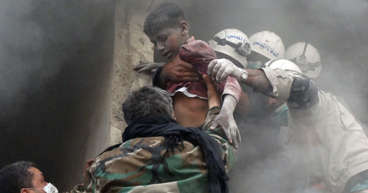 Emergency responders help evacuate a Syrian boy from a residential building reportedly hit by an explosives-filled barrel dropped by a government forces helicopter in the Shaar neighborhood of the northern Syrian city of Aleppo.</p>