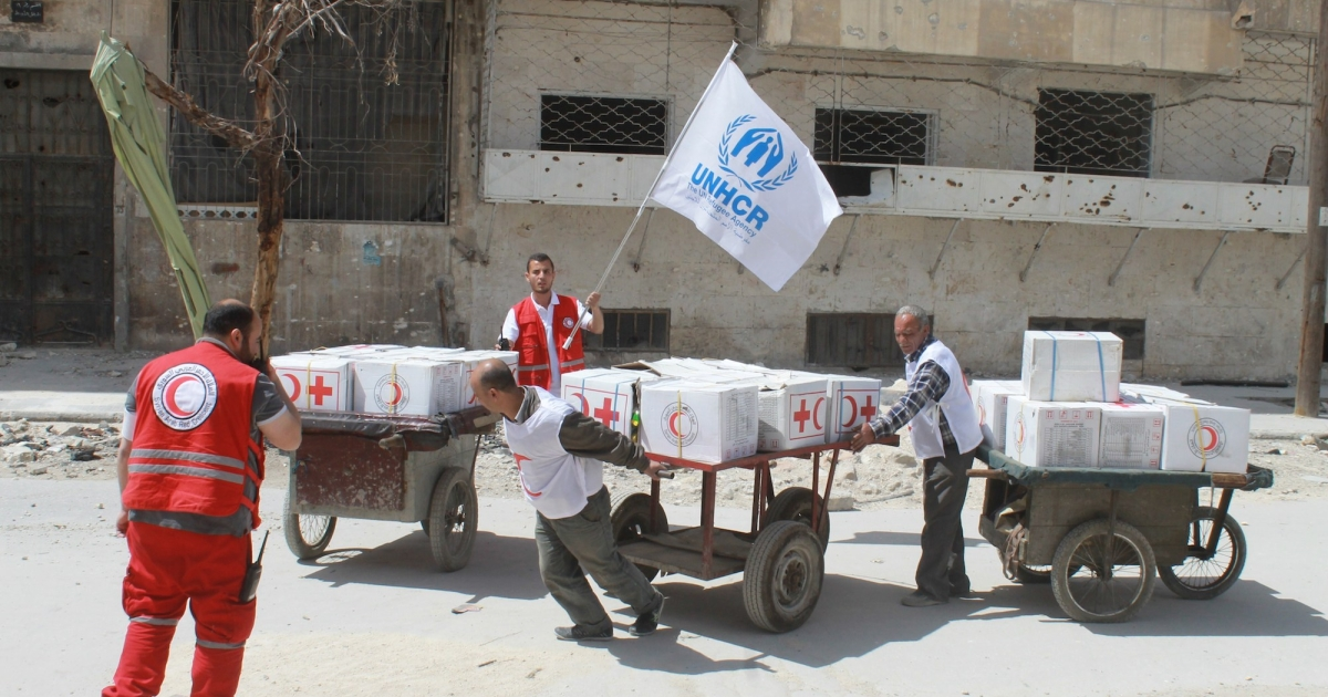 Members of the Syrian Red cross and Red Crescent cart aid to the rebel controlled Garage al-Hajz checkpoint in Aleppo, on April 8, 2014, after rebel forces and pro-government troops agreed to a cease fire to allow the aid in.</p>