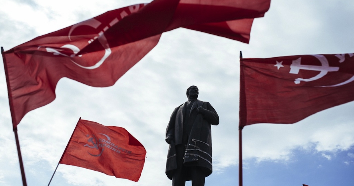 Supporters of the Ukrainian Communist Party wave red flags in front of a statue representing Soviet Union's founder Vladimir Lenin in the eastern Ukrainian city of Lugansk on April 22, 2014, on the 144th anniversary of Lenin's birth.</p>