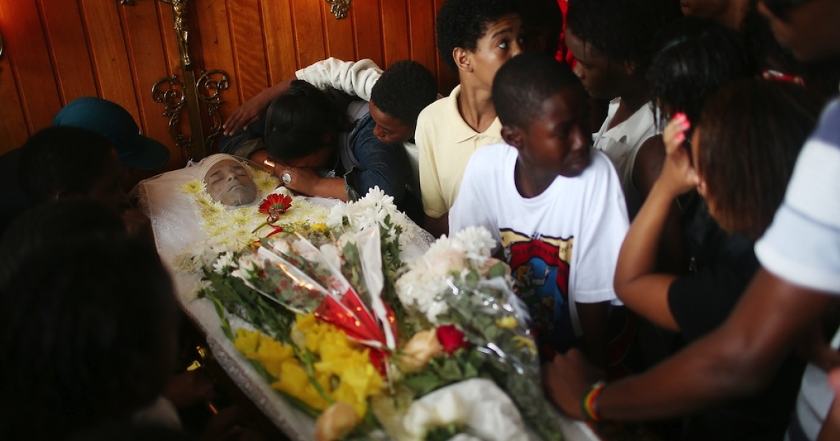 Mourners gather over the body of dancer Douglas Rafael da Silva at his funeral, after he was shot and killed, on April 24, 2014 in Rio de Janeiro, Brazil. Da Silva's body was discovered in the pacified Pavao-Pavaozinho community, just blocks from Copacabana Beach, on April 22. Protests and shootings broke out as a result after protesters alleged he was killed by police in the pacified 'favela'.</p>