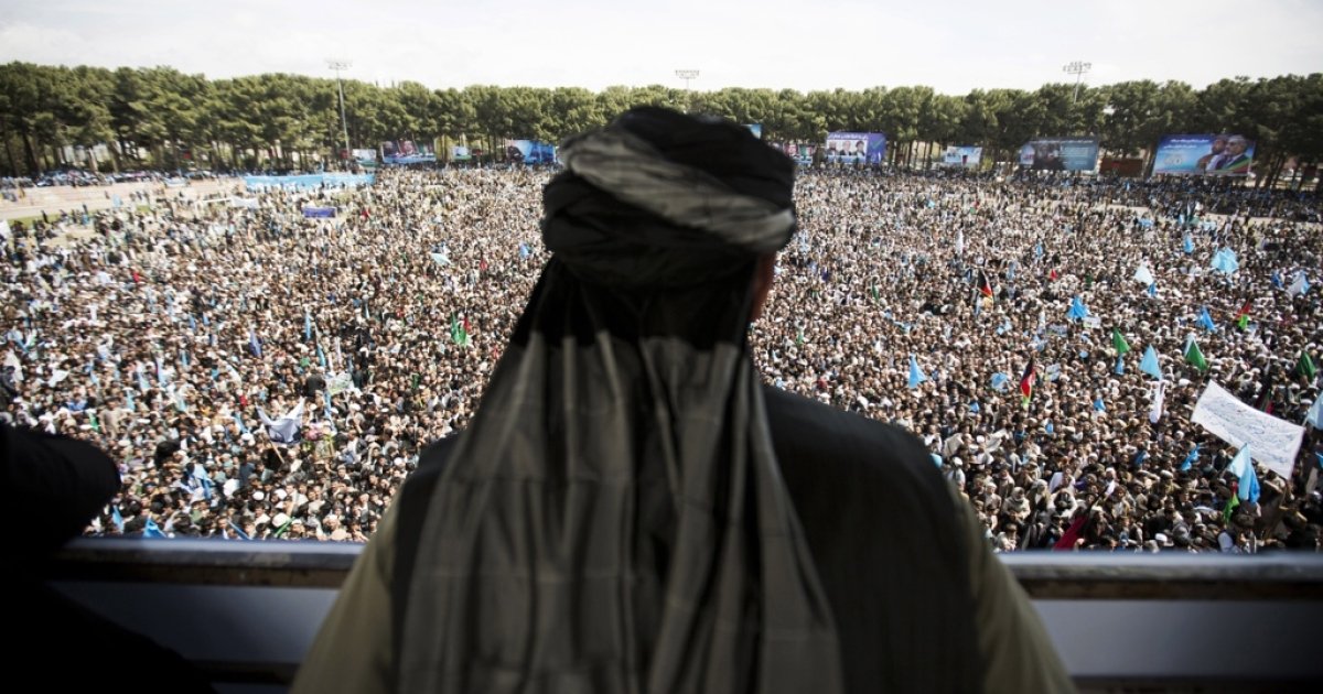 An Afghan man watches the crowd supporting presidential candidate Abdullah Abdullah.</p>