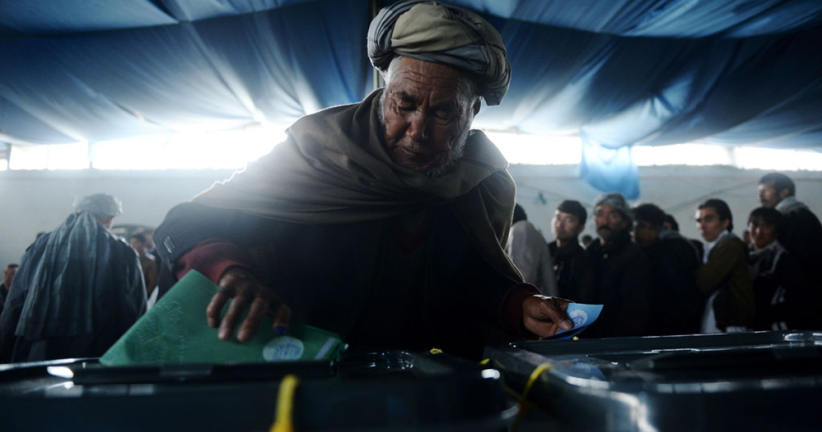 An Afghan man casts his vote at a local polling station in Kabul on April 5, 2014.</p>
