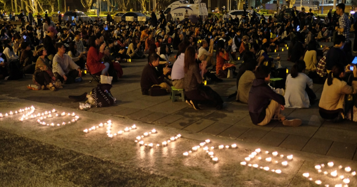 Protesters sit on the ground next to candles during an anti-nuclear demonstration in Taipei on April 24, 2014.</p>