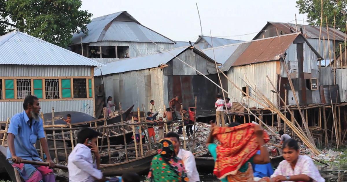 A boat carries people to Korail slum in Dhaka, Bangladesh</p>