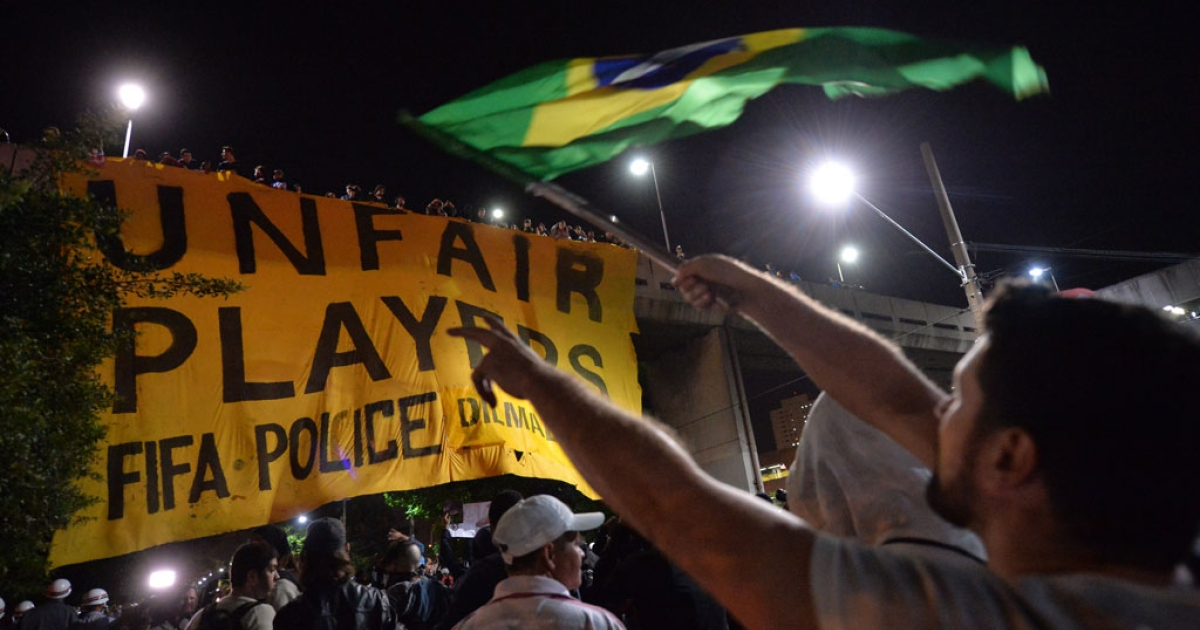 A demonstrator protests with a Brazilian national flag against the upcoming FIFA World Cup Brazil 2014 in Sao Paulo, Brazil on April 29, 2014.</p>