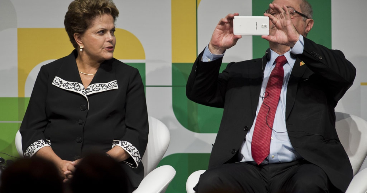 Brazilian Minister of Communications Paulo Bernardo Silva takes a picture next to Brazilian President Dilma Rousseff at the NETmundial conference in Sao Paulo on April 23, 2014.</p>