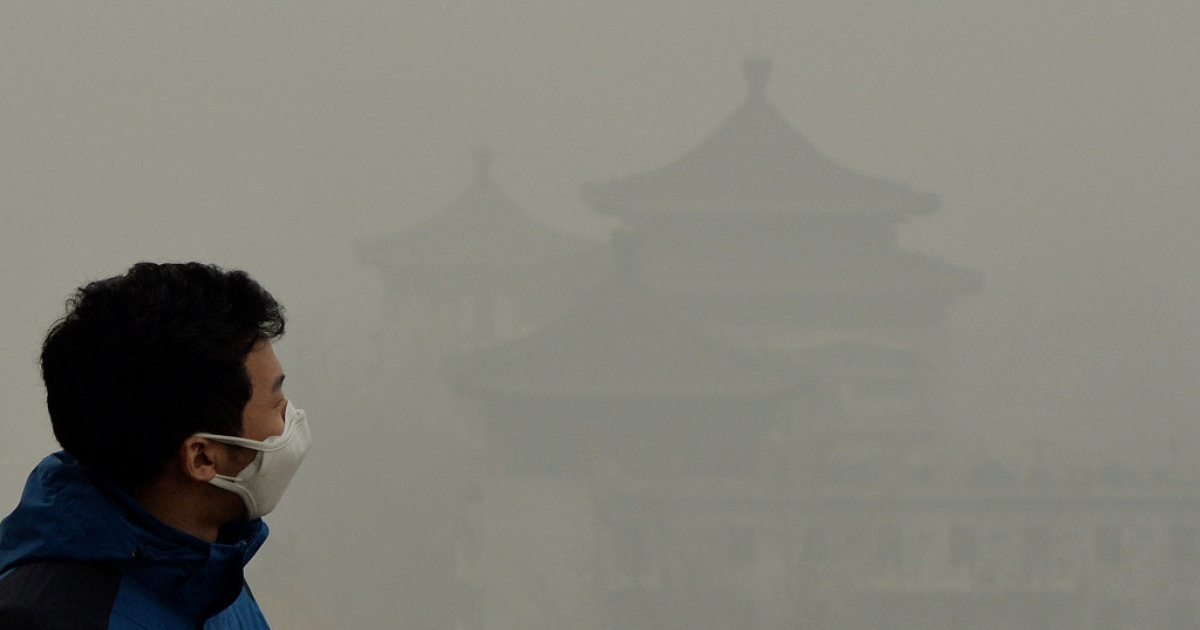 A tourist wearing a face mask climbs Jingshan Hill beside the Forbidden City as heavy air pollution continues to shroud Beijing.</p>