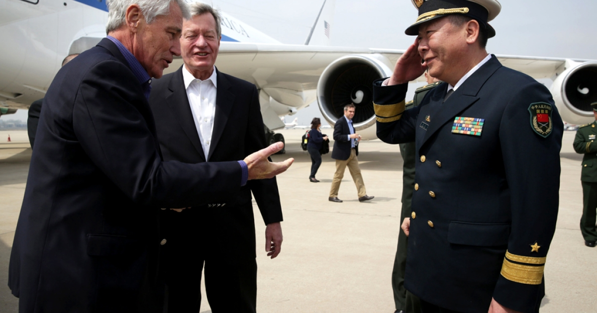 US Secretary of Defense Chuck Hagel is welcomed by Rear Admiral Guan Youfei, Director of Foreign Affairs Office of the Chinese Defense Ministry and US Ambassador to China, Max Baucus, upon his arrival at Qingdao International Airport on April 7, 2014 in Qingdao, China.</p>