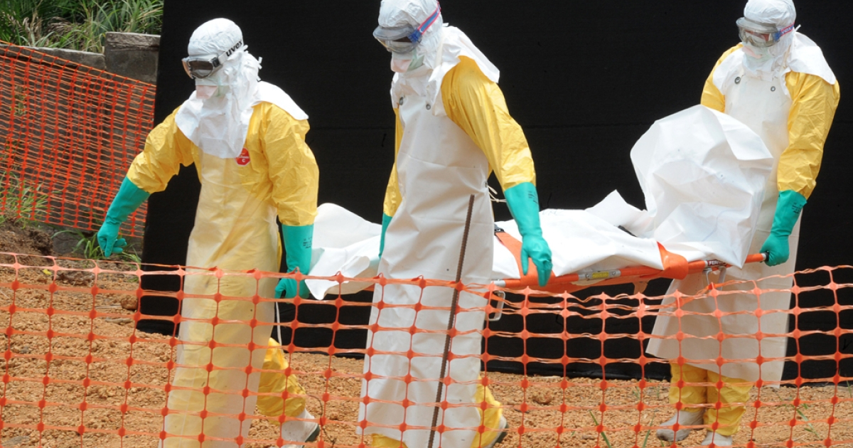 'Doctors without Borders staff carry the body of a person killed by Ebola virus in Guékedou, southern Guinea, on April 1, 2014.</p>