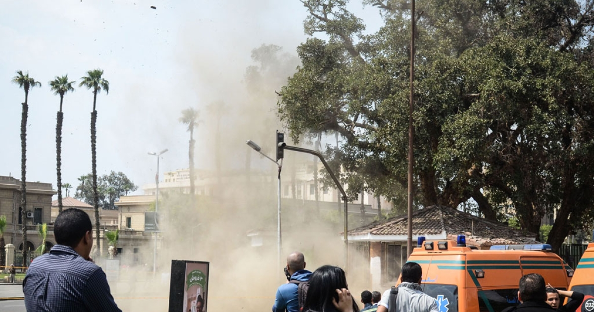 Egyptians look on as a bomb struck a police post near Cairo University in the center of Egypt's capital on April 2, 2014, which was followed by two further blasts.</p>