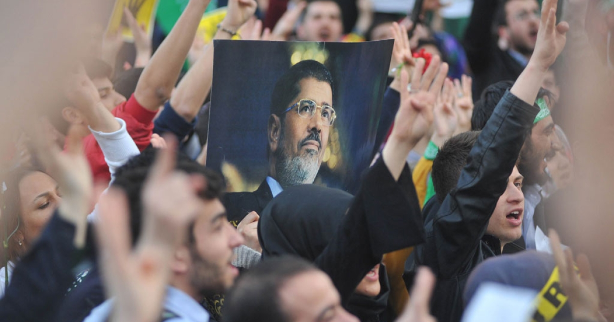Supporters of the Egyptian Muslim Brotherhood hold a portrait of deposed president Mohamed Morsi in a rally on April 9, 2014.</p>